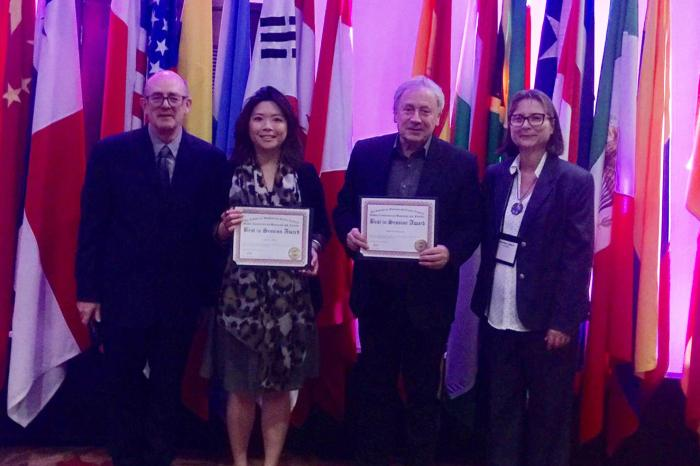 Lynsie Chew (middle left) and Alan Parkinson (middle right) collect their award at the Global Conference on Business and Finance
