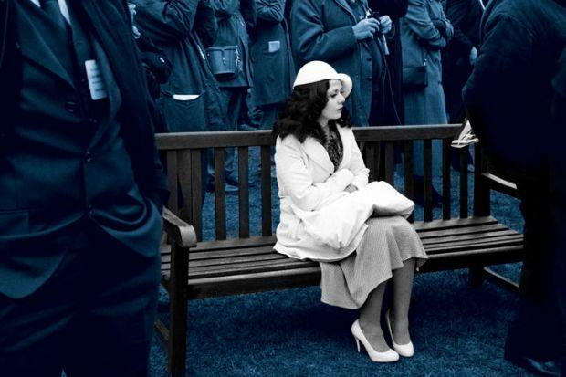 Woman in all white sat on a bench with people stood around. Blue hue to the picture.
