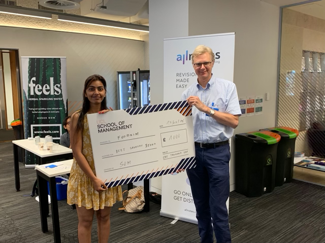 Supriya Rai, left, collects her £1000 cheque from Programme Director Simon Hulme.