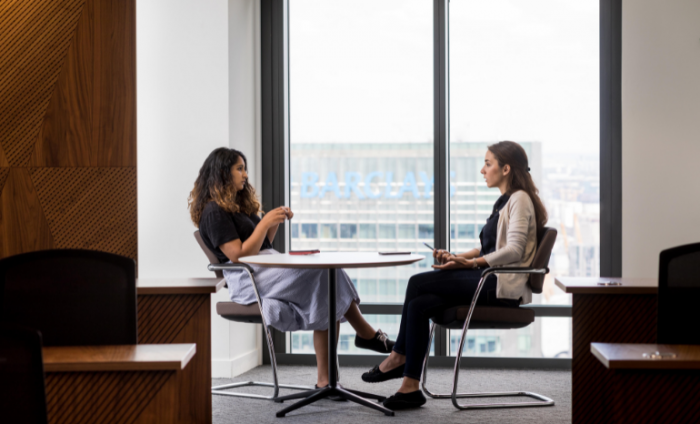 Two women sat opposite each other over a table discussing work in a skyscraper building with a view of London in the background