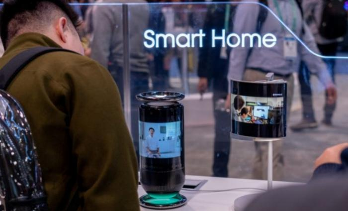 Man standing at a tech exhibit examining a new Smart Home camera product