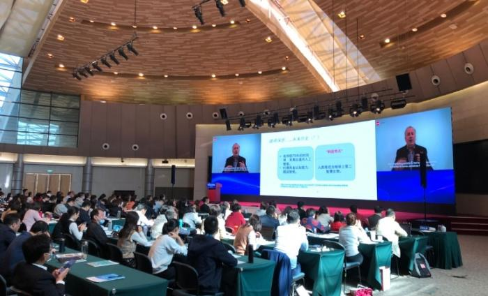 Photo of male speaker on big digital screens delivering a talk to the audience at a forum in Shanghai