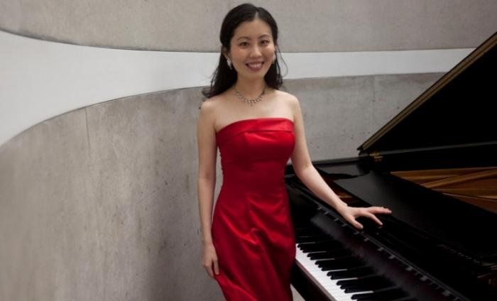 Photo of Chia-Jung Tsay standing next to a grand piano smiling