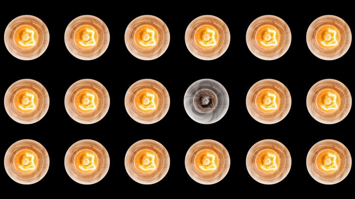 18 light bulbs with only 17 switched on and one switched off on a black background