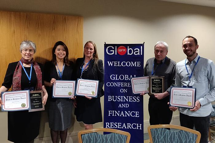 Photo of the staff who won a Finance Award holding their certificates. From left to right: Magda David Hercheui, Lynsie Chew, Danusia M. Wysocki, Alan Parkinson, and Elliot Guner