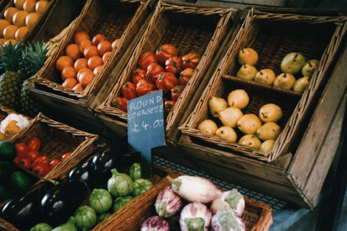 A photo of organic fruit and veg on sale in brown crates.