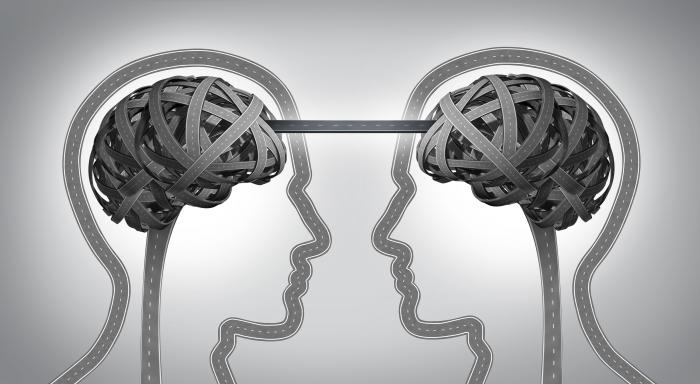 Black and white of two heads silhouettes facing each other with the brains linked to represent psychological contract